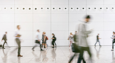 Wall Mural - large crowd of anonymous blurred people walking in a modern hall