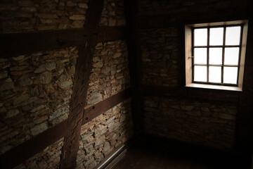 Light shines through window into dark lonely cellar.
