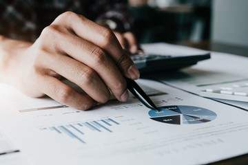 Close up of bookkeeper of Accountant hand with pen pointing on paper for calculating report. Business Financial Concept