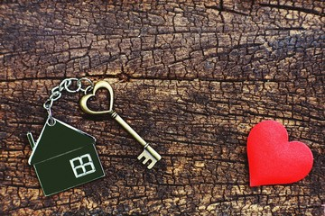 Home key with love house keyring decorate with mini heart on wood background, sweet home concept