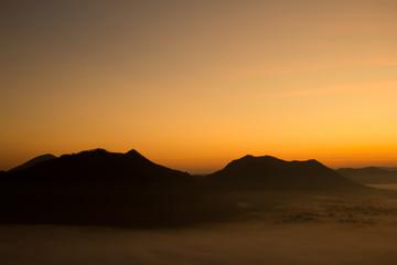 Beautiful sky sunrise. Mountain layer in morning sun ray and winter fog.