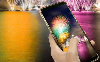 Hand of a businessman holding a smartphone to take a pictures at night and fireworks on dark sky for design idea in your work.