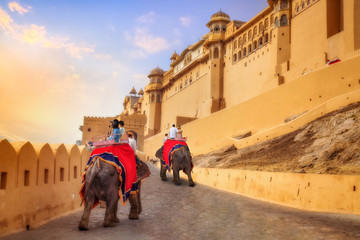 Tourist couple enjoy elephant ride at the historic Amer Fort at sunset. Amer Fort is a UNESCO World heritage site at Jaipur Rajasthan India.