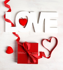 Word Love and red gift box at white background