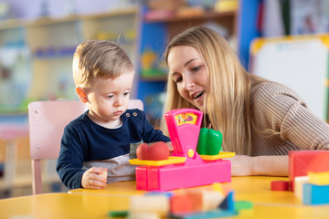 Little child boy and nursery teacher sit at table and play with toy scales in playroom