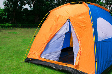 Orange and blue color family camping tent without rain fly setup on green park campsite.