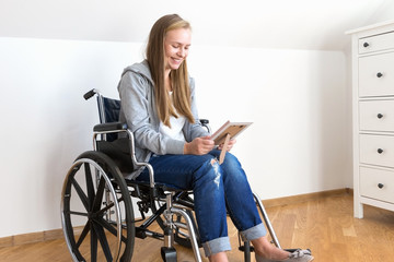 Disabled woman is looking at the photo in frame and smiling.