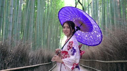 Fototapete - Asian women in traditional japanese kimonos is smiling and happiness at Bamboo Forest in Kyoto, Japan.