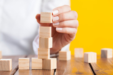 Woman hand arranging wooden cubes