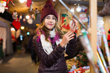 girl staying at market with small Christmas trees