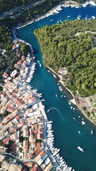Aerial drone bird's eye view photo of iconic small safe port of Gaios with traditional Ionian architecture and sail boats docked, Paxos island, Ionian, Greece