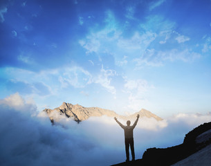 Man raises hands standing on the top of mountain. Victory and sucsess