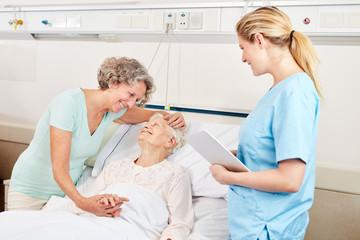 Frau macht Krankenbesuch bei einer Seniorin