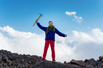 Man holds ice ax and celebrate succesfull climb to the top