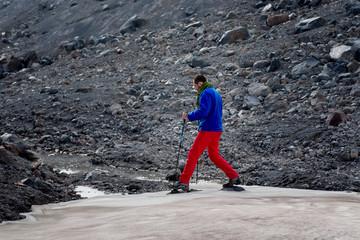 Man in touristic equipment moves over glacier