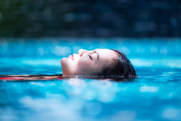 Young asian woman relaxing in swimming pool at spa resort.relaxing,spa relax,bikini concept.