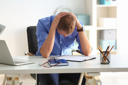 Man having panic attack at workplace in office