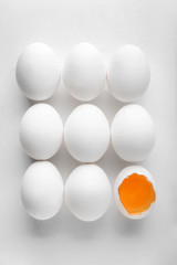 Cracked and whole chicken eggs on white background