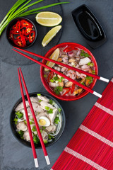 Ceramic bowls of asian  soup with shrimp, noodles, spring onion, sliced egg and mushrooms, served with chopsticks. Top view.