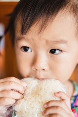 child little girl eating sticky rice in plastic bag
