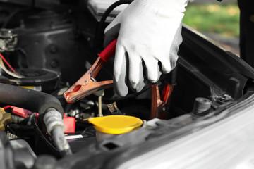 Male mechanic charging a car battery