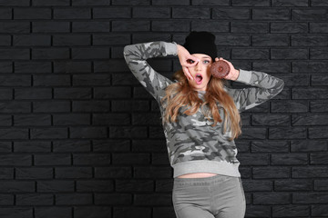 Funny young woman with tasty donut on dark brick background