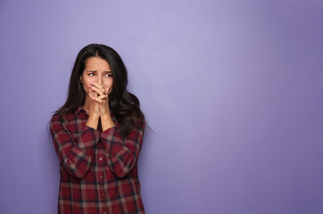 Stressed young woman on color background