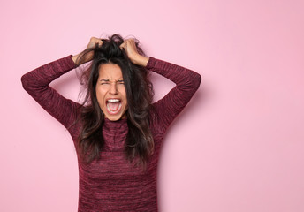 Screaming young woman on color background