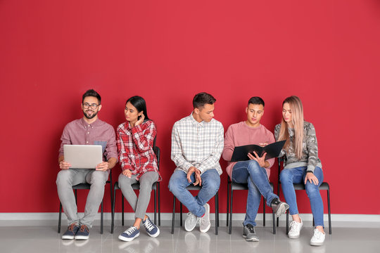 Young students sitting near color wall
