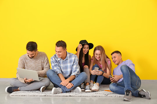 Young students sitting on floor near color wall