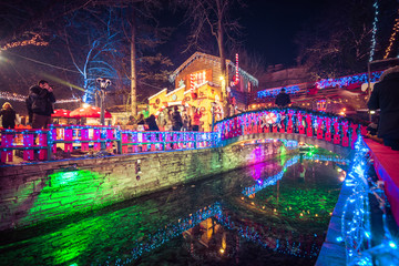 "Night view of the greek Christmas market ""Oneiroupoli"" with lights, figurines around the river in Drama, Greece"