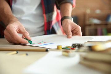 Young artist drawing at table in office