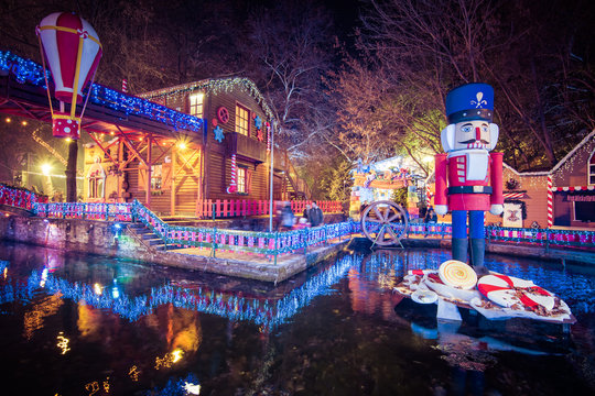 """Night view of the greek Christmas market """"Oneiroupoli"""" with lights, figurines around the river in Drama, Greece"""