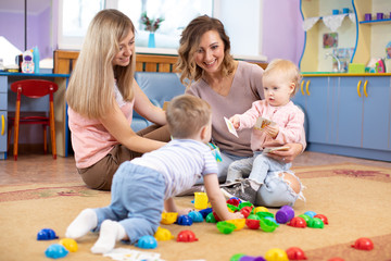 Babies play and their mothers communicate in playroom
