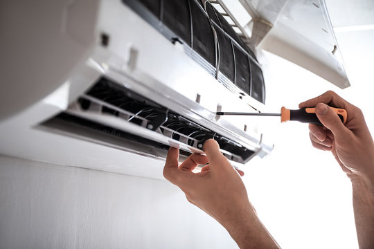 Electrician repairing air conditioner indoors