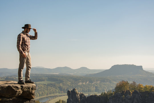 Young bearded male traveler in hat stand on the cliff in sunny day