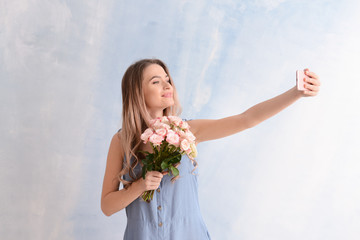 Beautiful young woman with bouquet of flowers taking selfie on color background
