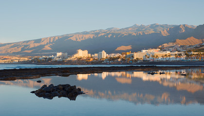 Early morning light over the south-west coast of the island, towards the most popular resorts in Costa Adeje for entertainment, eateries and nightlife, in Las Americas, Tenerife, Canary Islands, Spain