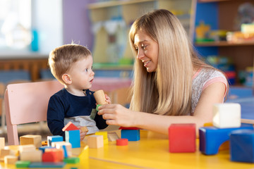 Cute woman and baby boy playing educational toys at creche or nursery