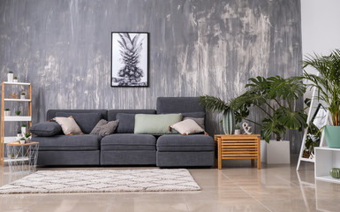 Stylish interior of living room with comfortable grey sofa
