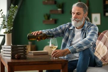 Senior man drinking wine at home