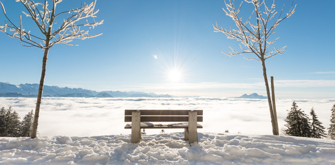 Bench in the snowdrifts. Clouds below under the feet. Rigi. Switzerland.