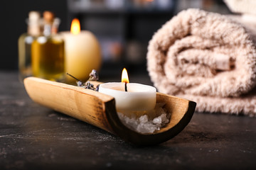Burning candle and sea salt on table in spa salon