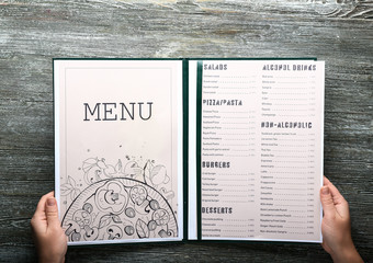Female hands with menu on wooden table Wall mural