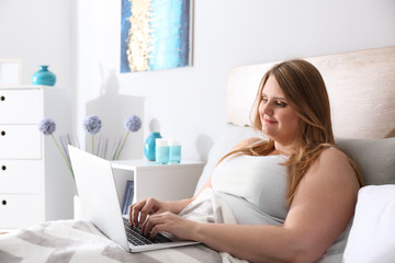 Beautiful plus size girl with laptop resting at home. Concept of body positivity