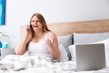 Beautiful plus size girl talking by mobile phone at home. Concept of body positivity