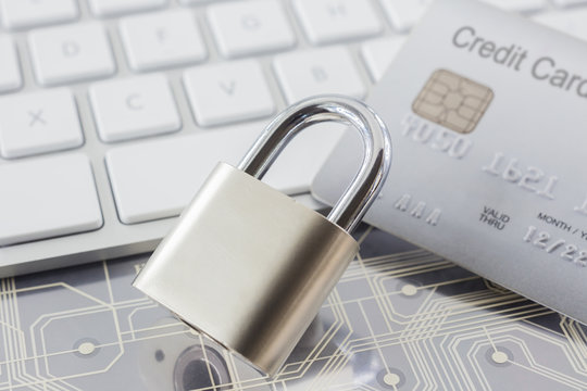 Padlock and credit card on keyboard and electronic circuits.