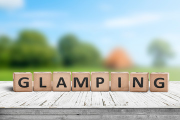 Glamping sign on wooden planks in the summer