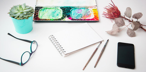 Set of watercolor paints,  brushes for painting and blank white paper sheet of sketchbook on white background. Graphic design adviser consulting with young designer at classroom for banner
