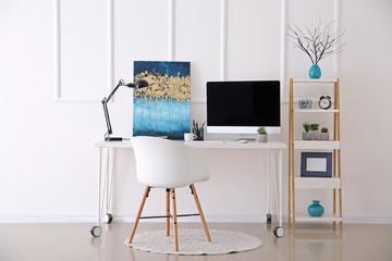 Stylish workplace with modern computer near white wall
